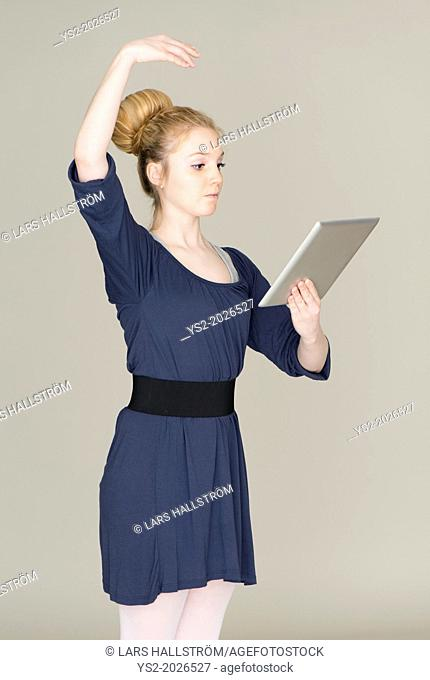 Young blond female teenager in ballet dress holding a tablet pc