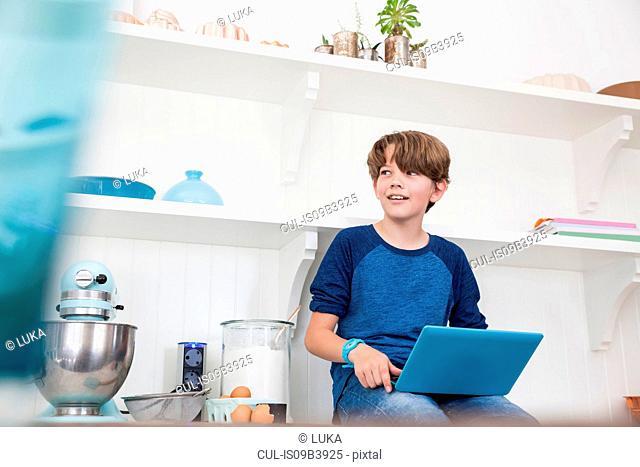 Boy sitting on kitchen work surface, using laptop computer