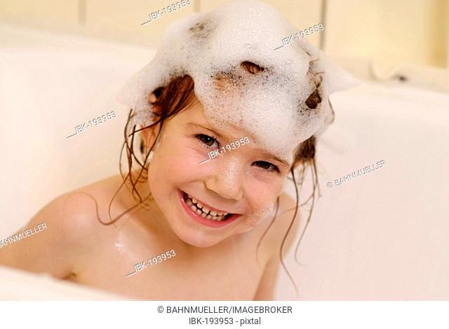 Child in the bathroom having a foam bath