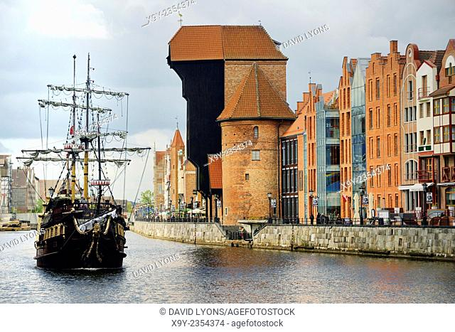 Gdansk Poland. Old Town. Medieval Crane Gate rises over the Motlawa River and historic buildings on the Dlugie Pobrzeze