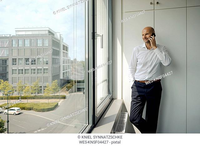 Smiling businessman standing in his office, talking on his mobile phone