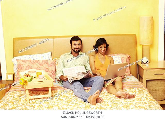 Portrait of a mature man sitting on the bed with a mature woman using a laptop beside him