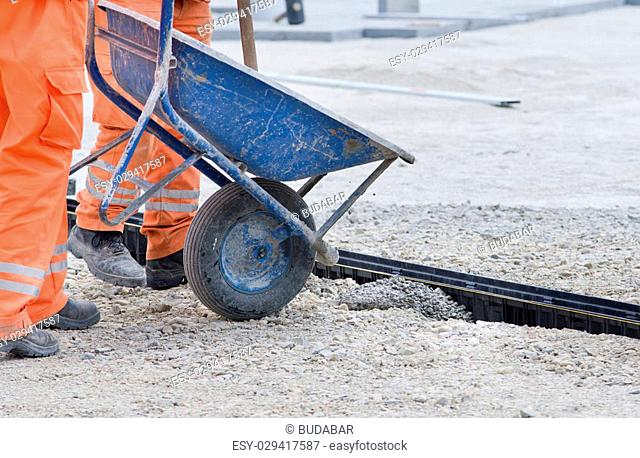 Construction worker pouring concrete from wheelbarrow to install drainage pipe in ground