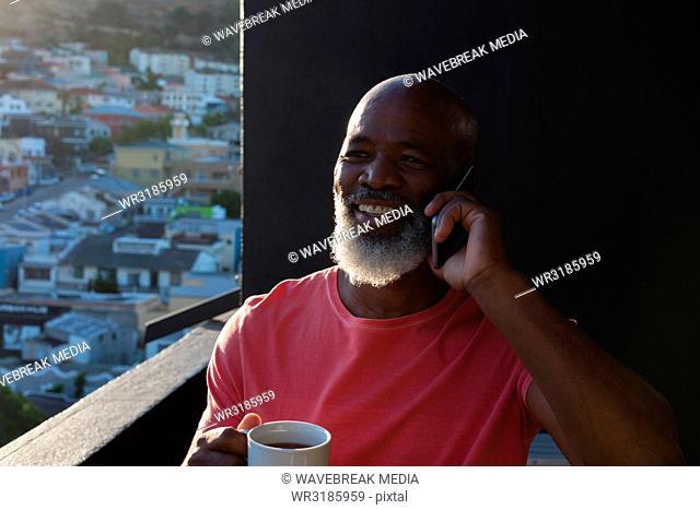 Senior man having coffee while talking on mobile phone