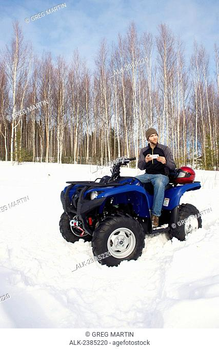 Man on ATV with smart phone in Fairbanks, Interior Alaska, Winter