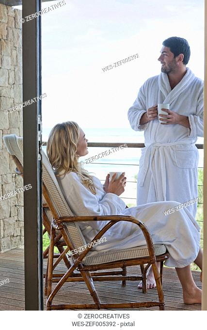 Young couple wearing bathrobes on patio at beach house