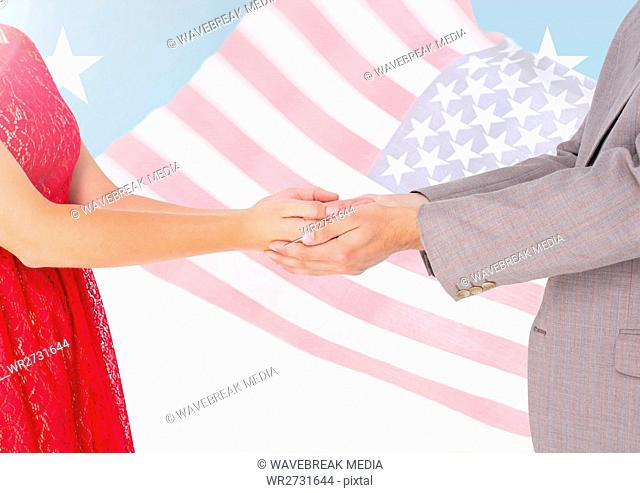 Composite image of couple holding hands against american flag