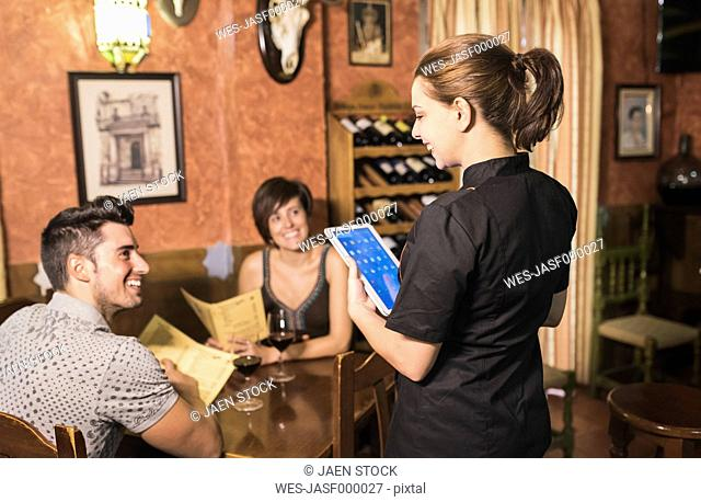 Waitress taking the order of couple in restaurant with digital tablet