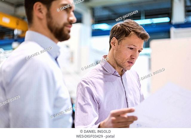 Two men in factory looking at plan