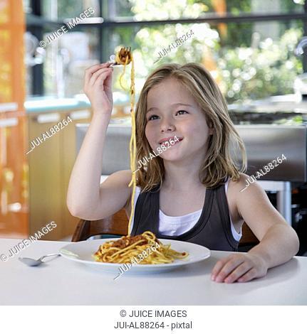 Girl eating pasta at table