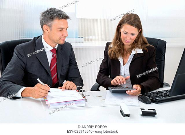 Two Businesspeople Calculating Tax Together At Desk In Office