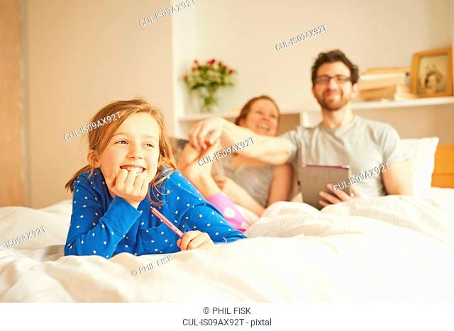 Mid adult couple tickling daughters bare feet whilst having lie in