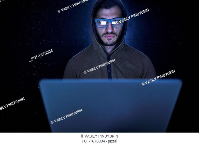Serious computer hacker wearing hooded shirt using laptop against black background
