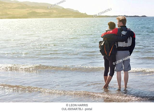 Mid adult couple with arms around each other on beach, Loch Eishort, Isle of Skye, Hebrides, Scotland