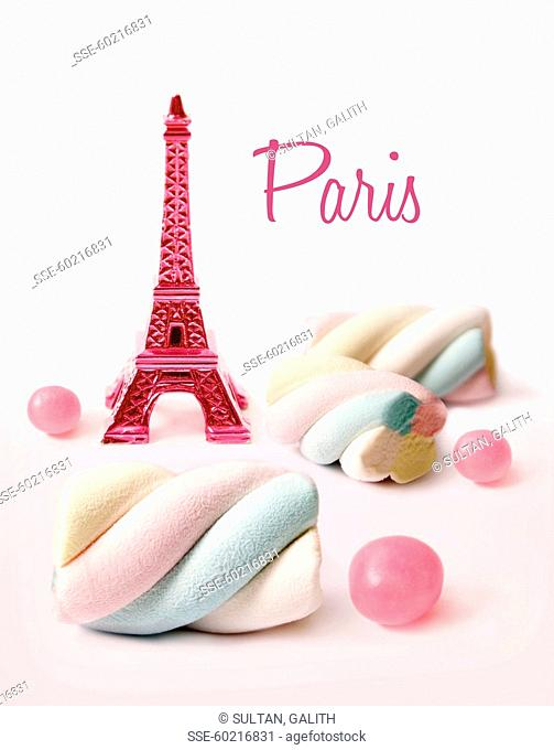 Composition with a mini pink Eiffel Tower, jelly beans and marshmallows on a white background
