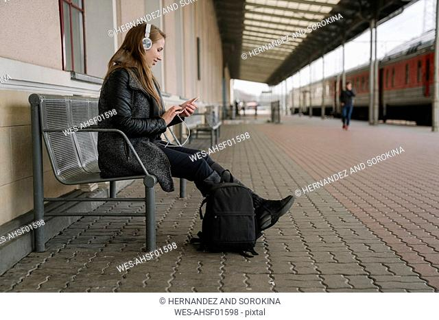 Smiling young woman with backpack sittting on platform using smartphone and headphones, Vilnius, Lithuania