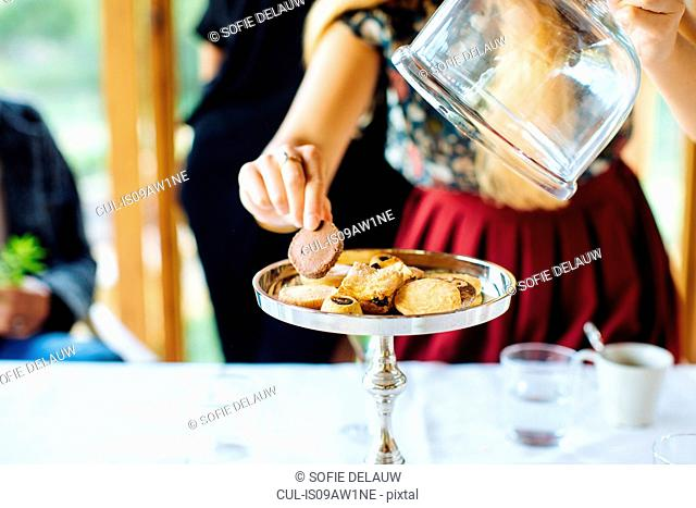 Woman selecting biscuit from cake stand in restaurant, Italy