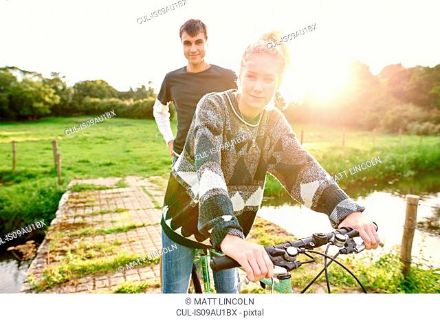 Portrait of young couple on bicycle at river footbridge
