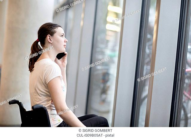 Young woman using wheelchair gazing through entrance window talking on smartphone
