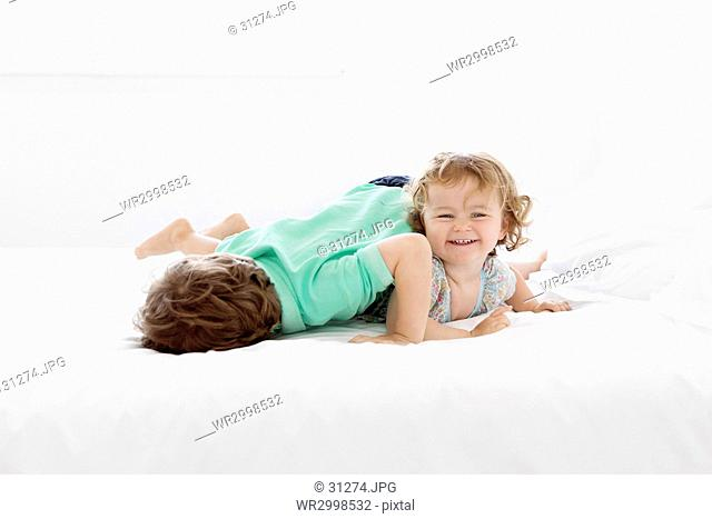 Two children lying on a bed at home, a three year old girl and a five year old boy