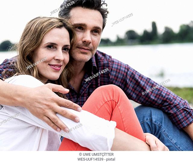 Affectionate happy couple sitting at the riverside
