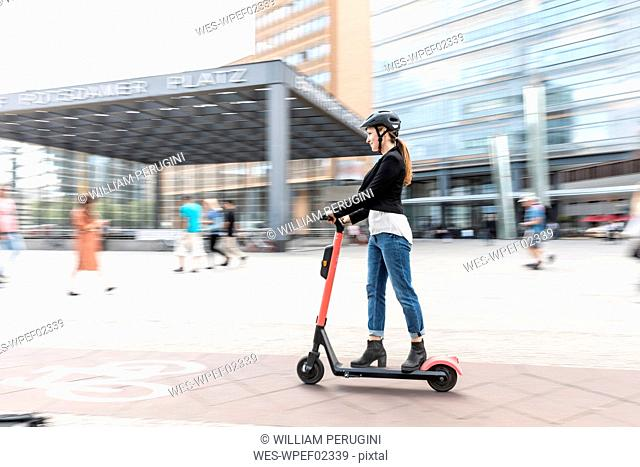 Woman riding e-scooter in the city, Berlin, Germany, Berlin, Germany