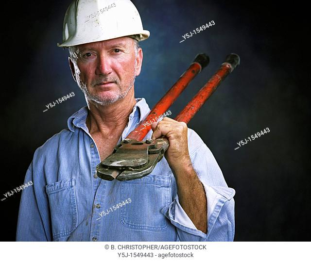 Middle-aged laborer holding bold cutters