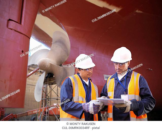 Workers talking on shipbuilding site