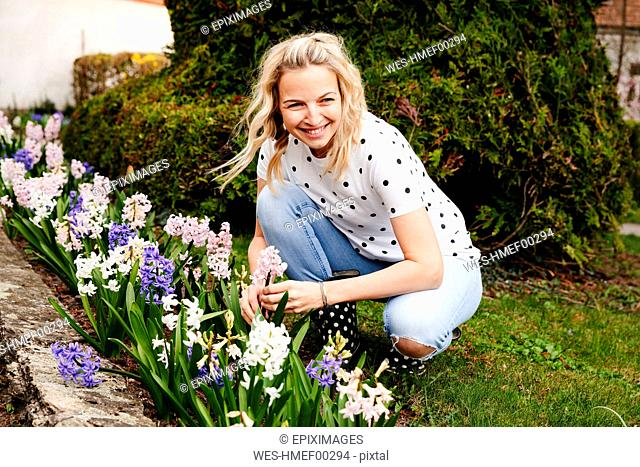 Young blonde woman controls hyacinths in her garden