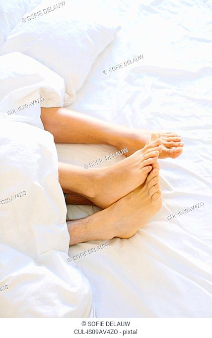 Young couples bare feet sticking out from duvet
