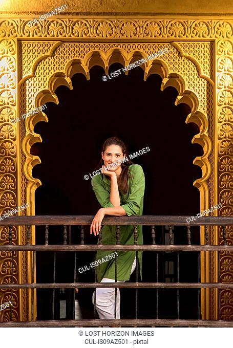 Woman in ornate doorway looking at camera smiling, Marrakesh, Morocco