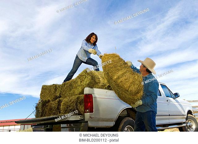 Hispanic couple loading hay onto truck