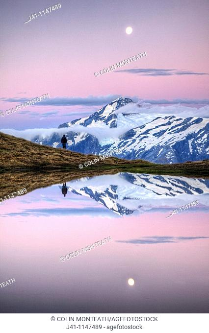 Mt Aspiring, tramper enjoys moonrise at dusk, Cascade Saddle tarn, Mount Aspiring National Park, Otago, New Zealand
