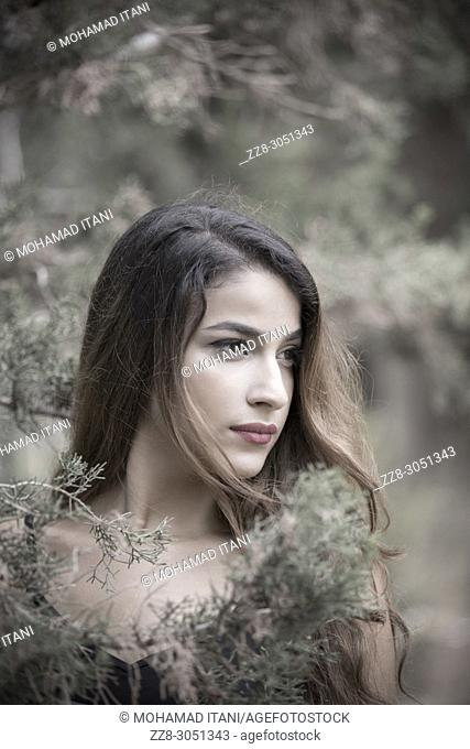 Beautiful young woman standing in the woods looking away