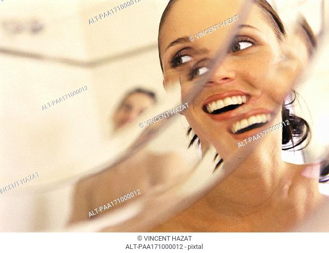 Woman looking at man in mirror, close-up, smiling, distortion