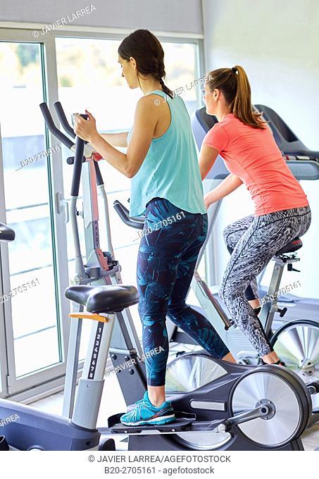 Women training in gym, Elliptical bike