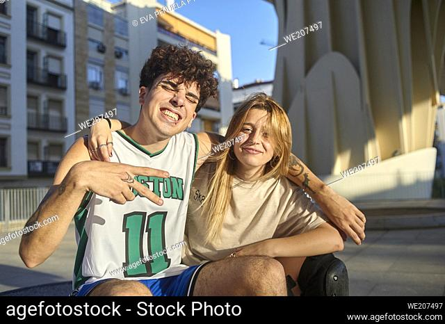 Young couple smiling at the camera in the city