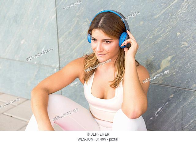 Portrait of smiling young woman listening music with cordless headphones