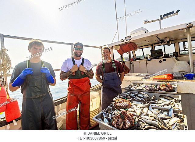 Portrait of three fishermen standing on boat
