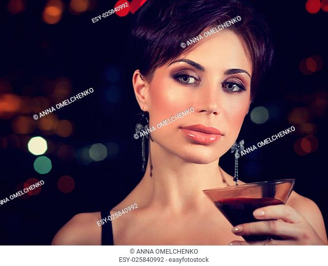 Portrait of beautiful brunet woman on the party, holding in hand glass of martini, spending evening in night club, celebrating New Year
