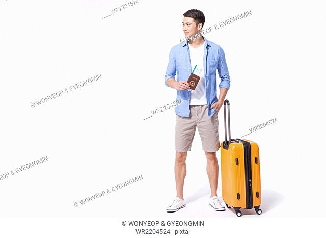 Man in casual outfits standing with his passport and flight ticket next to his suitcase and looking aside