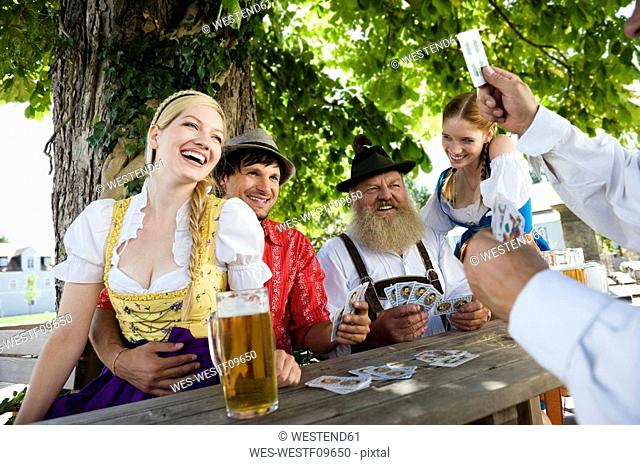 Germany, Bavaria, Upper Bavaria, People playing cards in beer garden