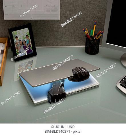 Hacker gloves opening laptop on office desk