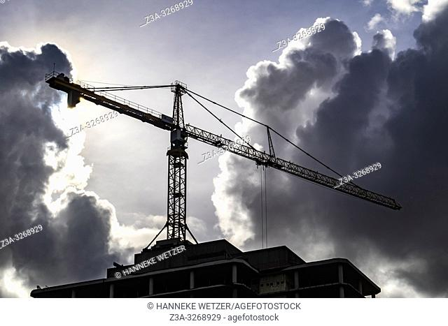 Construction site with crane against cloudy winter sky