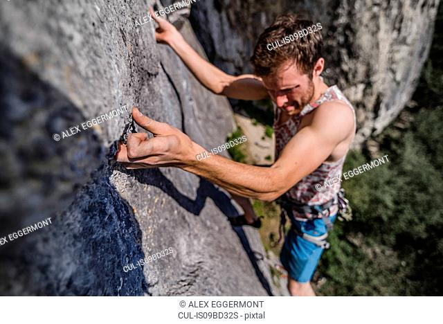 Young male rock climber climbing limestone rock face, Freyr, Belgium, high angle view