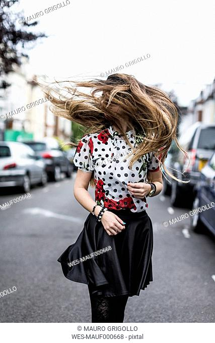 Stylished young woman shaking her hair