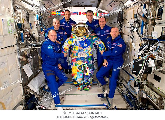 The six-member Expedition 53 crew poses for a portrait inside the Japanese Kibo laboratory module with the VICTORY art spacesuit that was hand-painted by cancer...