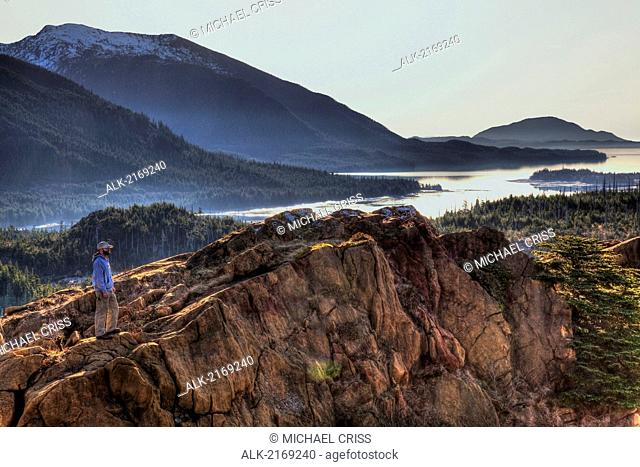 Scenic View Of Annette Island And Surrounding Coastal Area With Male Hiker In The Foreground, Inside Passage, Southeast Alaska, Spring. Hdr