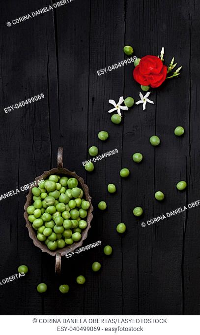 Artistic background with green peas and flowers on black color, flat lay, vertical composition