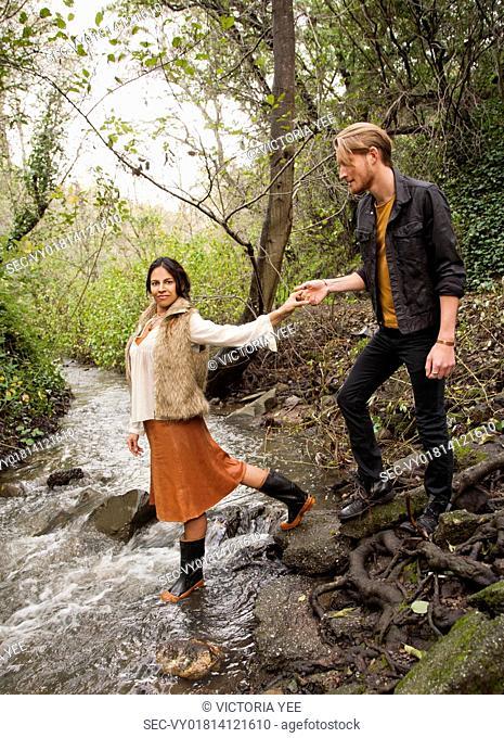 Woman helping man across creek